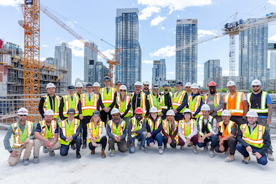 IMAGE: Executives and construction workers pose for a photo at The Well development in Toronto on Monday, June 3, 2019.