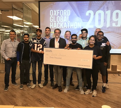 IMAGE: Kartik Budhiraja and his Build Stream team of hackers accept the first-prize cheque from Oxford executives following the Oxford Properties Hackathon in Toronto. (Kelly Roche RENX)