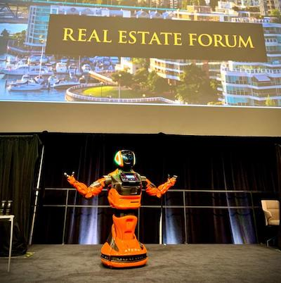IMAGE: GUS, an interactive robot using AI technology and presented by RYCOM, takes the stage during the Real Estate Forum in Toronto. (Courtesy RYCOM)